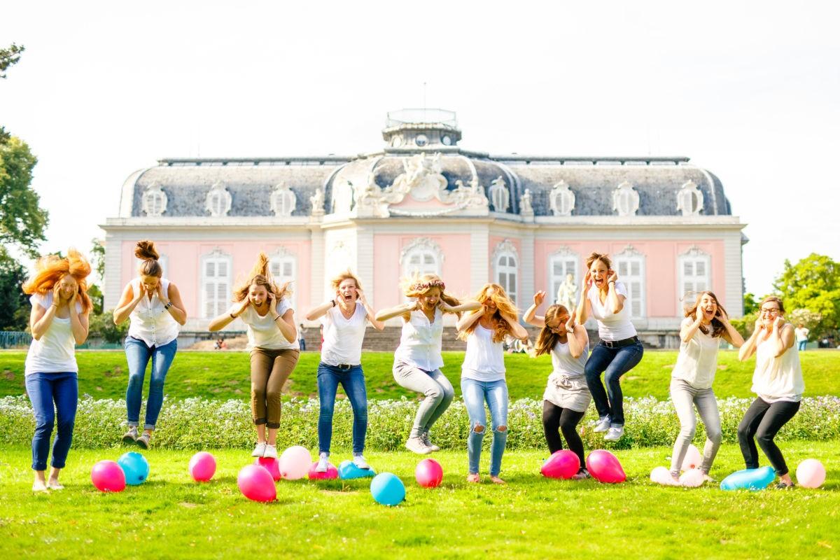 Eine Gruppe mädels hält sich die Ohren zu und springt gleichzeitig auf Luftballons drauf, um diese zum Platzen zu bringen.