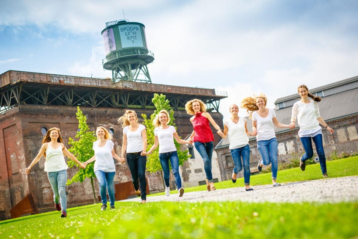 Acht Mädels laufen in einer Reihe auf die Kamera zu und halten sich dabei an den Händen