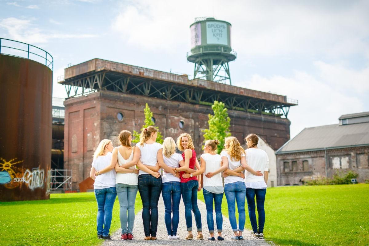 Eine Gruppe Mädchen steht in einer Reihe mit dem Rücken zur Kamera. Die Junggesellin in der Mitte dreht sich lachend um.