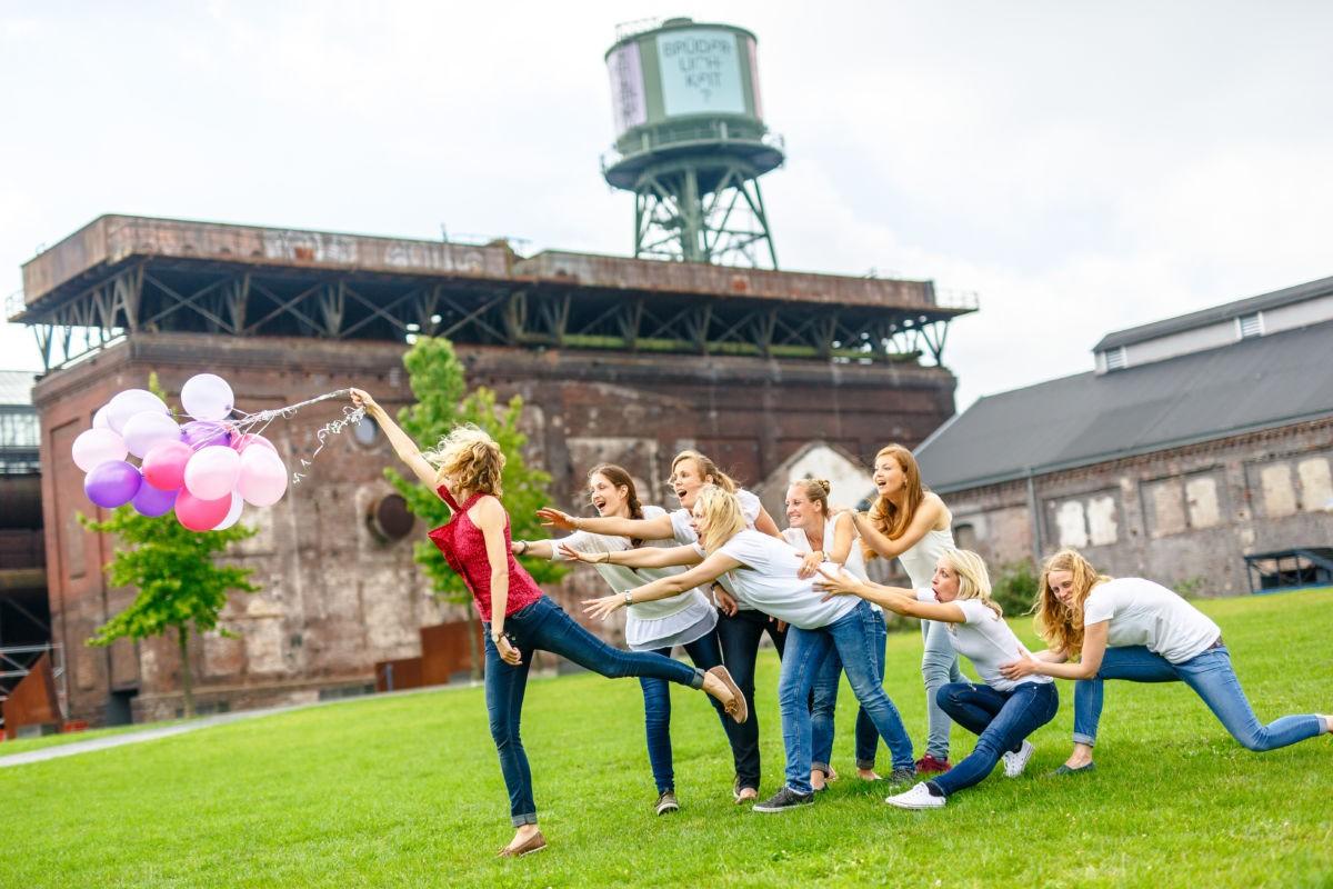 EIn Mädchen hält einen Haufen Luftballons in der Hand und scheint von ihnen fortgetragen zu werden. Weitere sieben Mädchen halten sie verzweifelt fest.