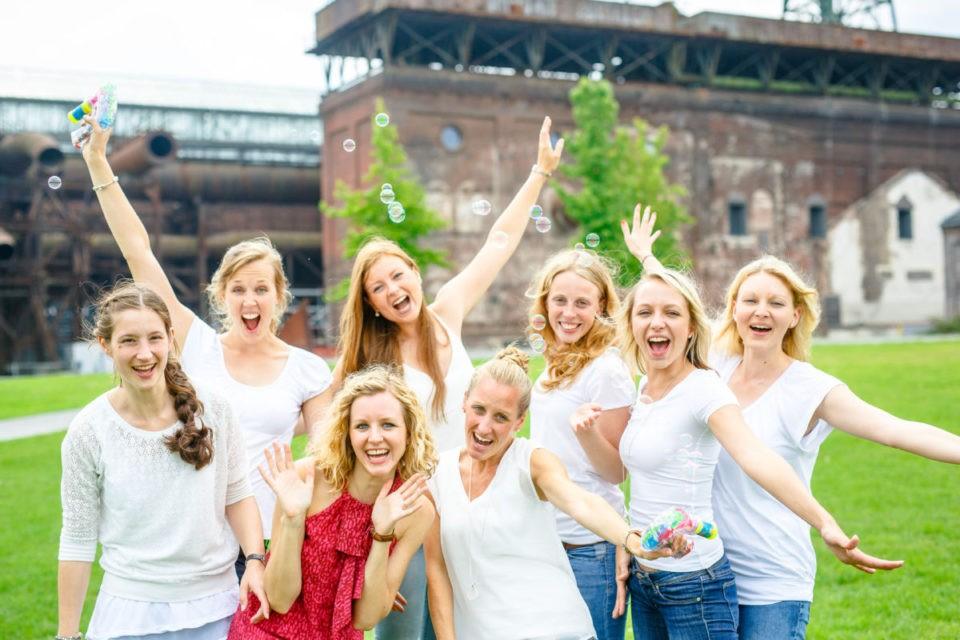 Gruppenbild mit acht Mädels, die in die Kamera lachen und Seifenblasen fliegen lassen.