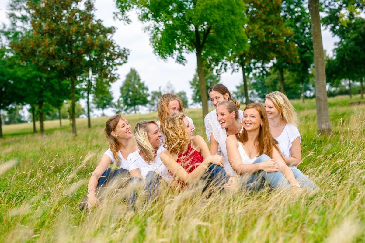 Eine Gruppe Mädchen sitzt im hohen Gras und lacht sich an