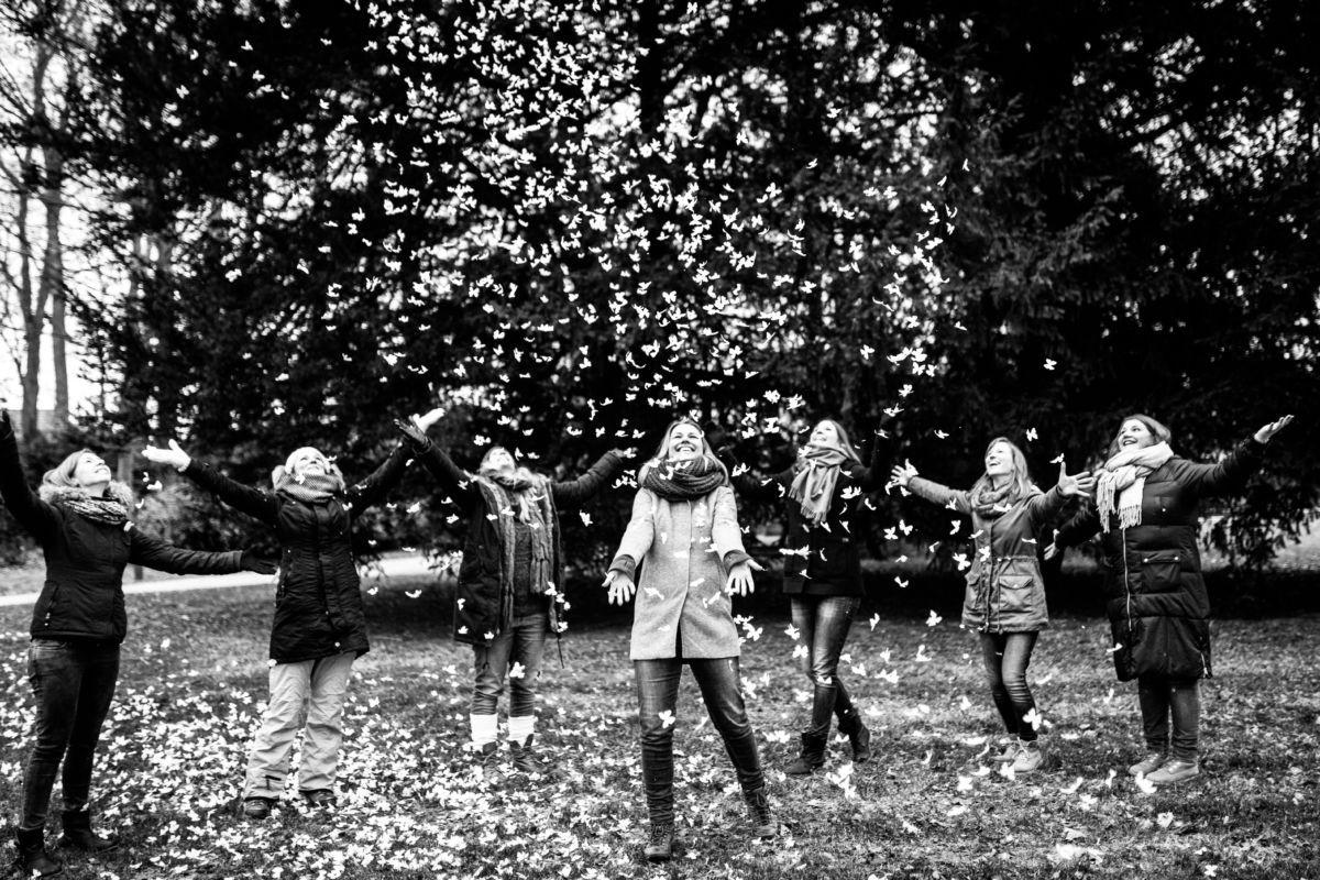Eine Gruppe Mädchen hälz lachend die Arme in die Luft, denn von dort regnet es Papier Schmetterlinge