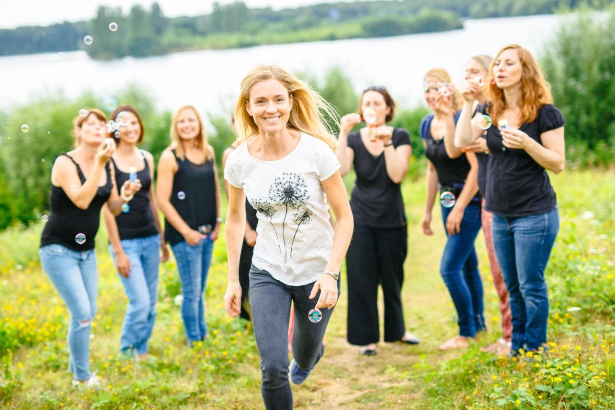 Ein Mädchen läuft auf die Kamera zu. Im Hintergrund stehen weitere Mädels, die Seifenblasen pusten.