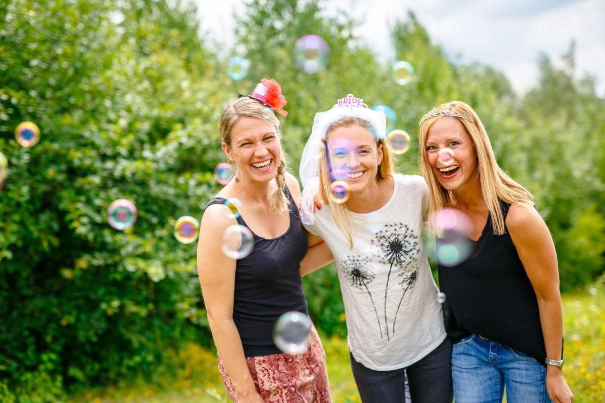 Drei Mädels halten sich im Arm und lachen in die Kamera.