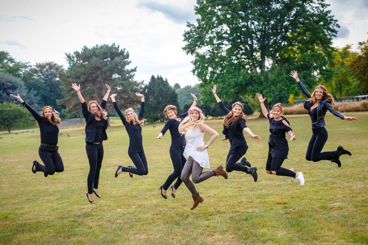 Acht Mädchen springen in die Luft. Sie tragen Blumenkränze.