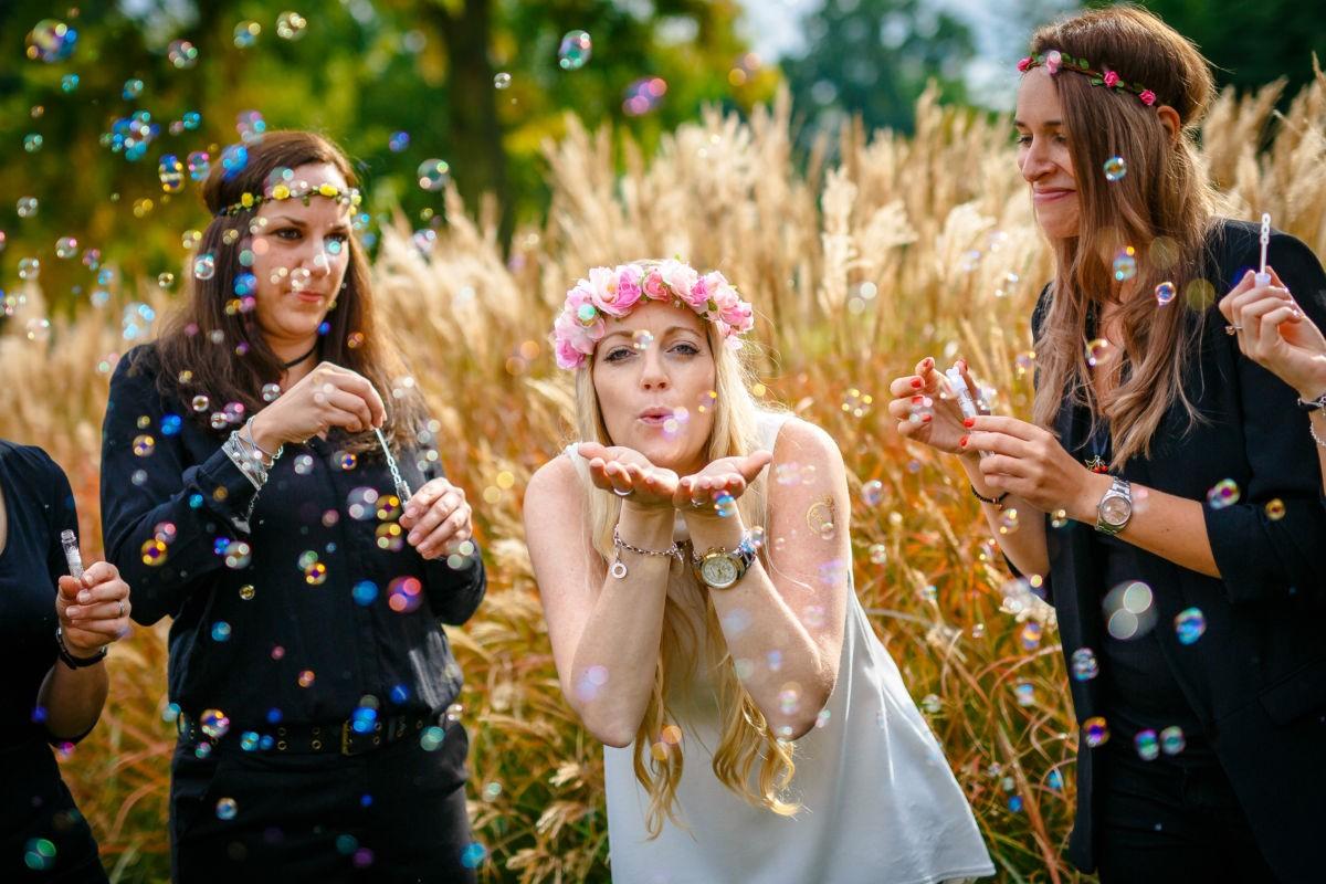 Die Braut in spe hat einen Blumenkranz auf und gibt ein Luftküsschen in die Kamera während ihre Mädels viele Seifenblasen pusten.