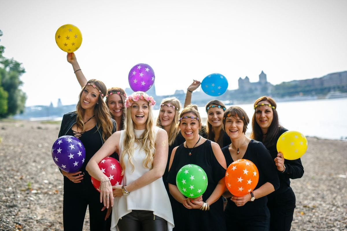 Eine Gruppe Mädels steht am Rheinufer und hält bunte Luftballons in den Händen.