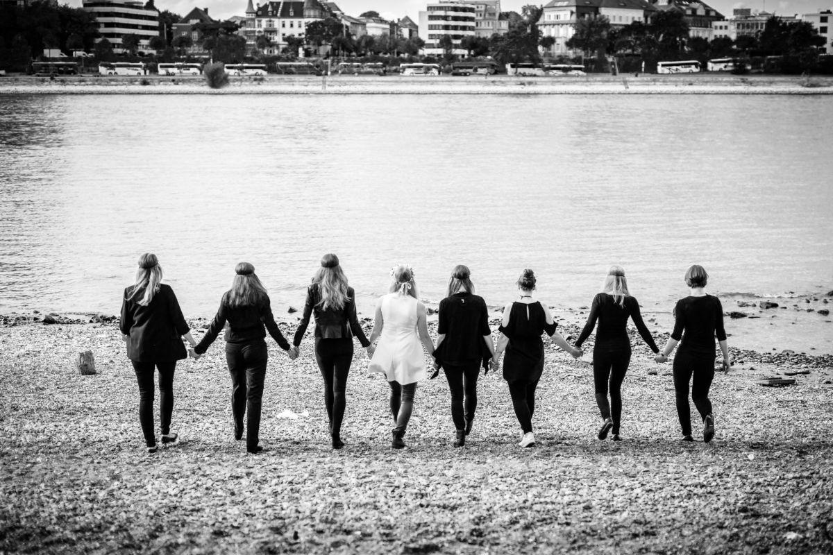 Acht Mädels laufen Hand in Hand auf einen Fluss zu.