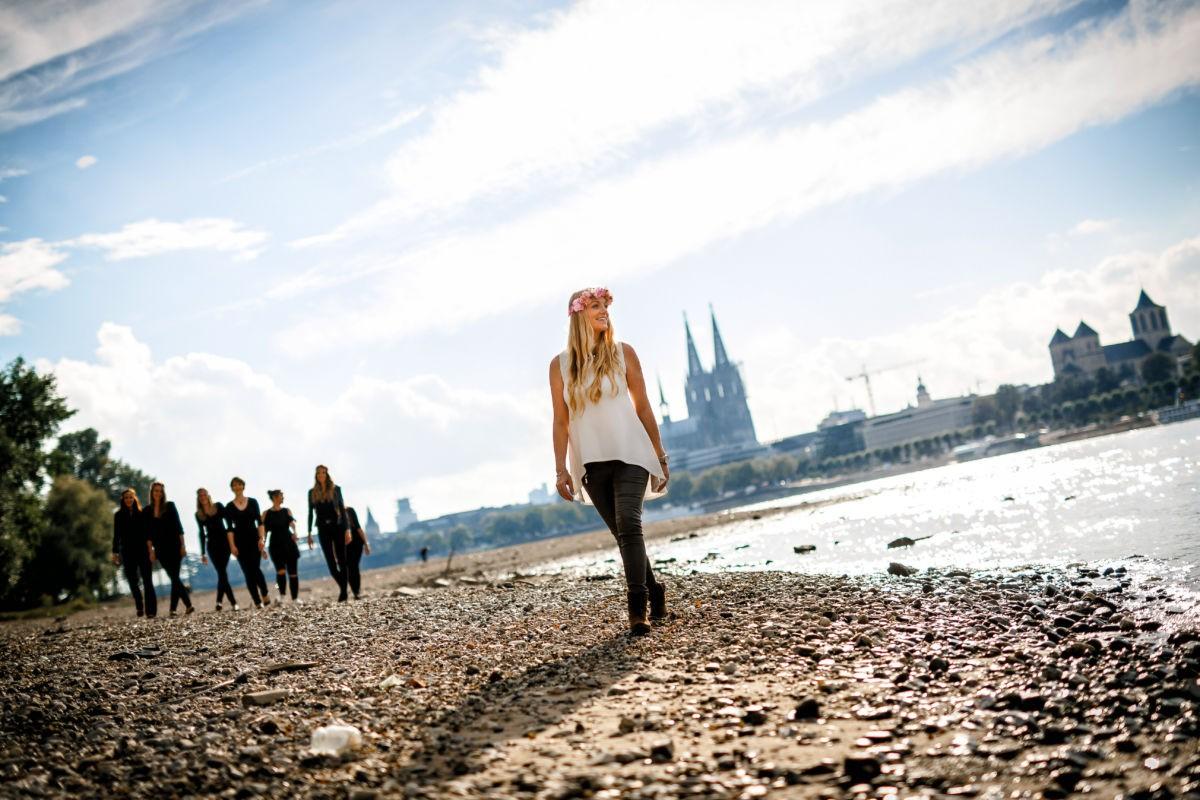 die Braut in spe läuft am Rheinufer entlang. Im Hintergrund ist der Kölner Dom zu sehen.