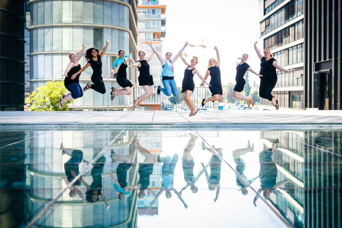 Eine Gruppe Mädchen springt im Medienhafen Düsseldorf in die Luft. Dabei spiegeln sie sich komplett in einem Wasserspiegel.