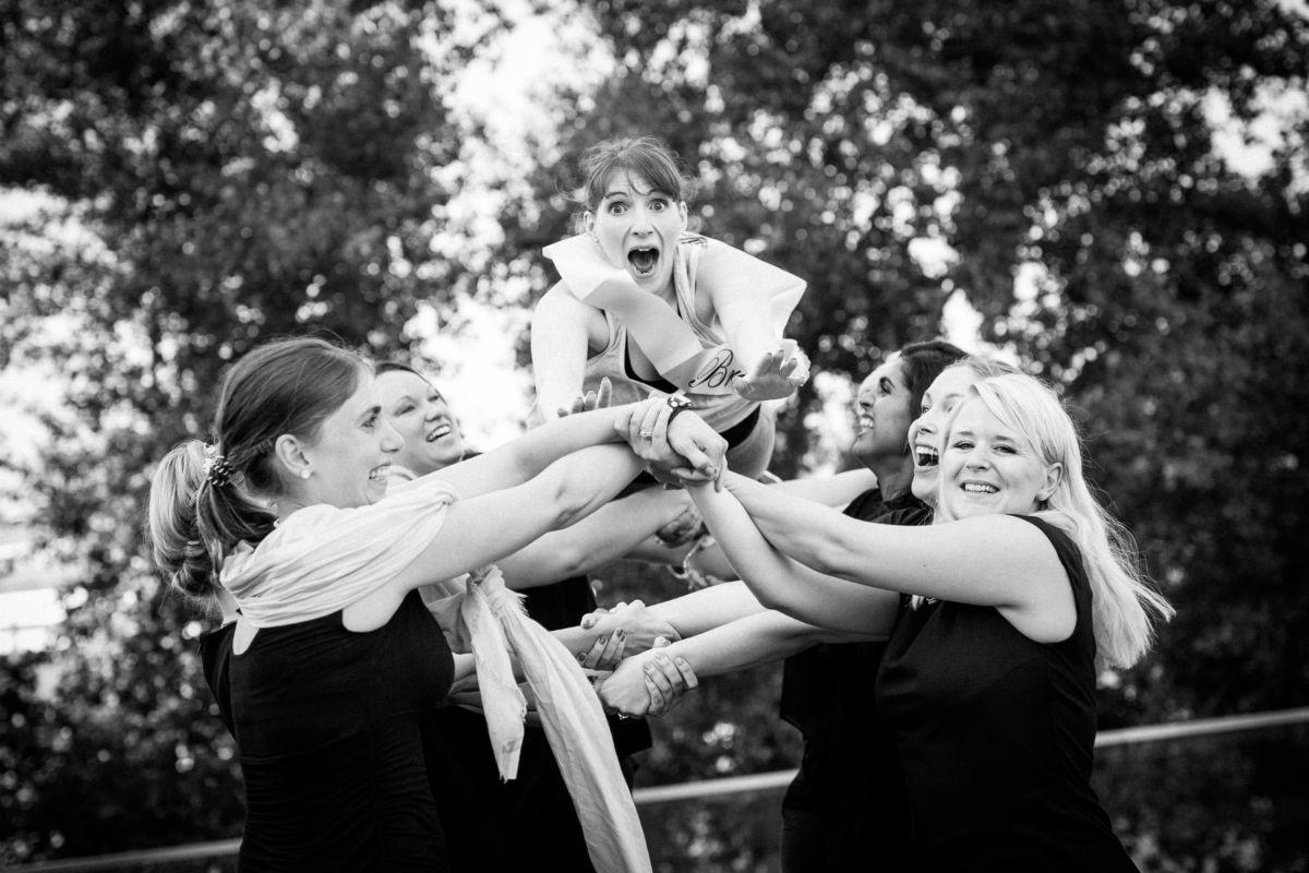 Eine Gruppe Mädels fängt die Braut in spe auf, welche laut schreit.