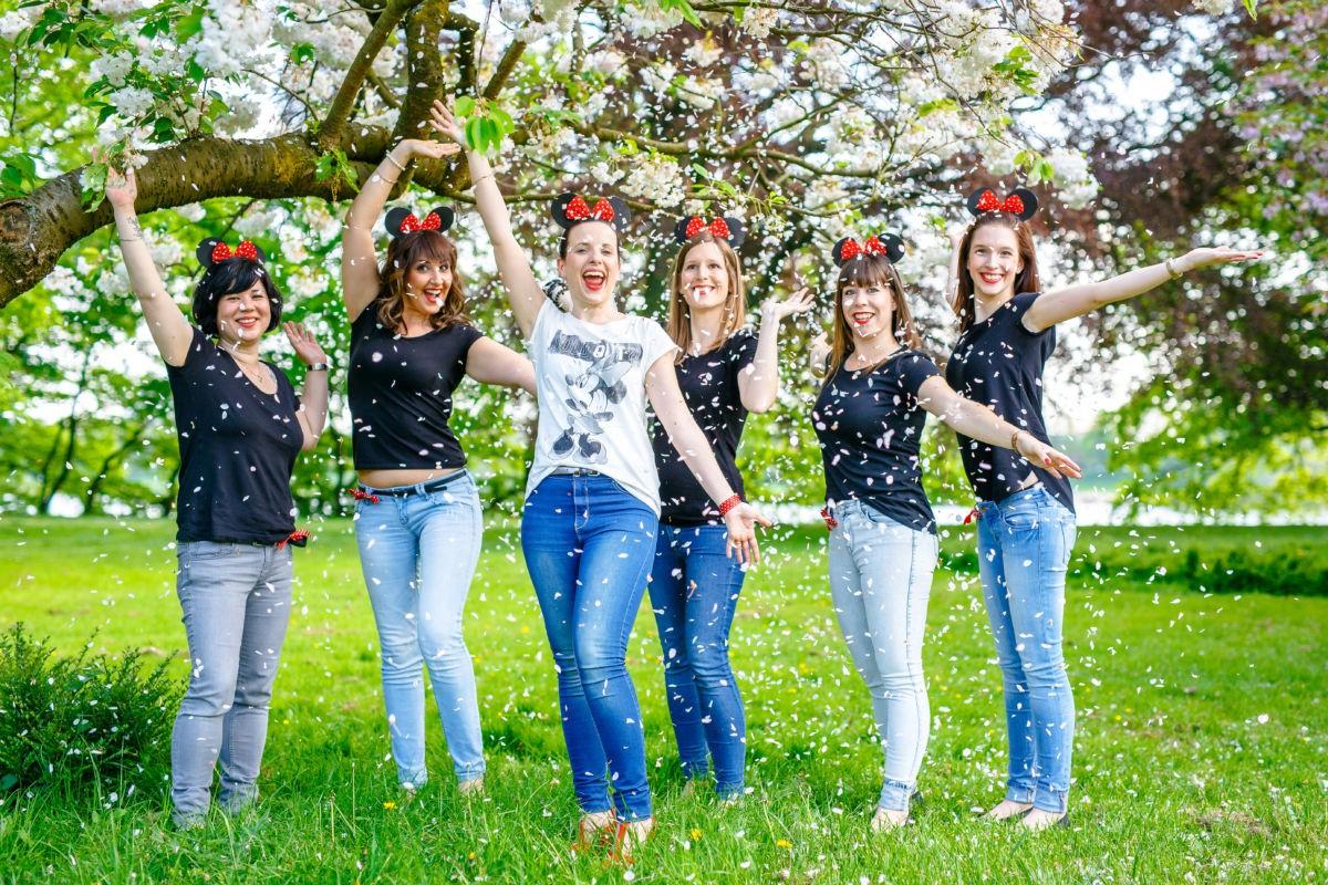 Sechs Mädels stehen unter einem Baum, von dem es Blüten regnet.