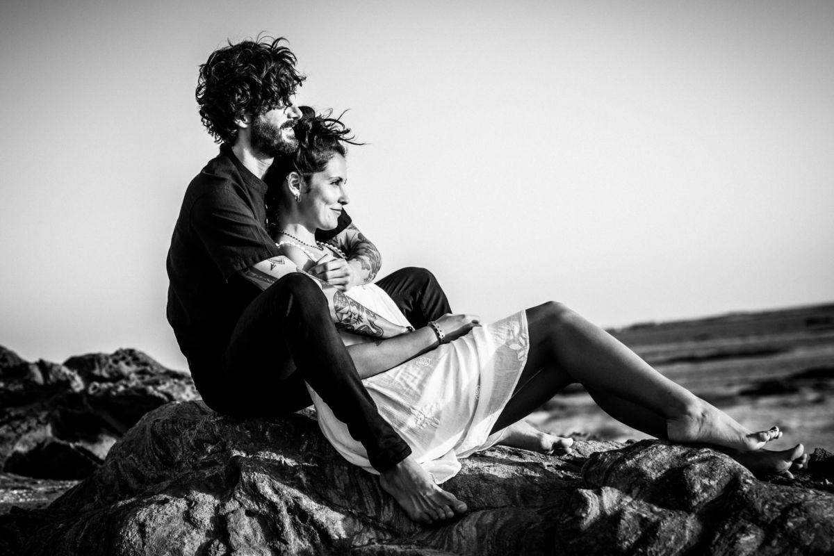 Engagementsfotos am Strand, das Paar kuschelt auf einem felden