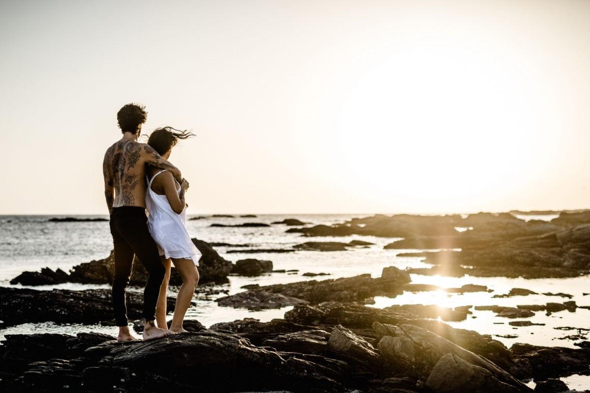 Paarfotos am Strand im Sonnenuntergang, das Paar sieht verträumt in die Sonne und ist von hinten zu sehen