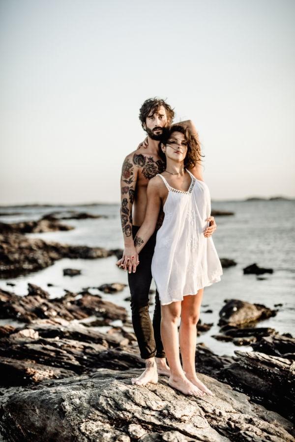 Das Paar steht auf einem Felsen am Meer und schaut in die Kamera