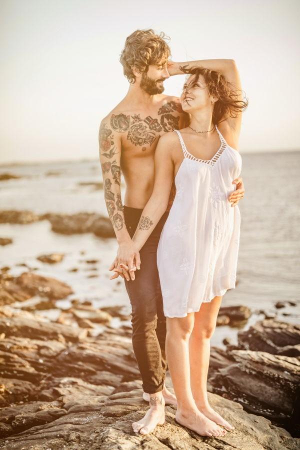 Das Paar steht für sein Verlobungsbild am Strand und sieht sich verliebt an