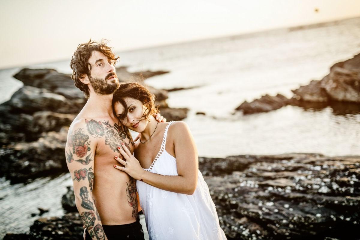 Das Paar steht am Strand auf einem Felsen mit dem Meer im Hintergrund. Die Frau sieht ind ie Kamera, der Mann über sie hinweg. Engagement Shooting mit ROCKSTEIN fotografie