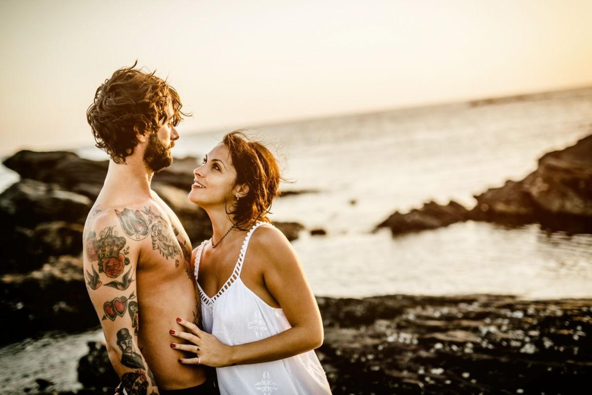 Das Paar sieht sich verliebt an, Wind zerzaust ihr Haar, sie stehen für ihre Paarfotos am Strand