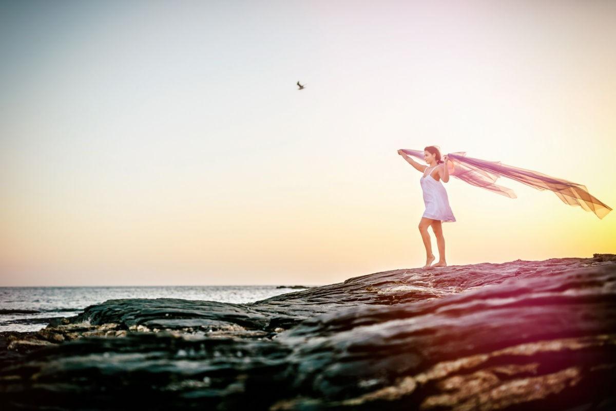 Eine Frau steht im weißen Kleid auf einem Felsen am Meer. Sie hält ein Tuch in die Luft, das im Wind weht.