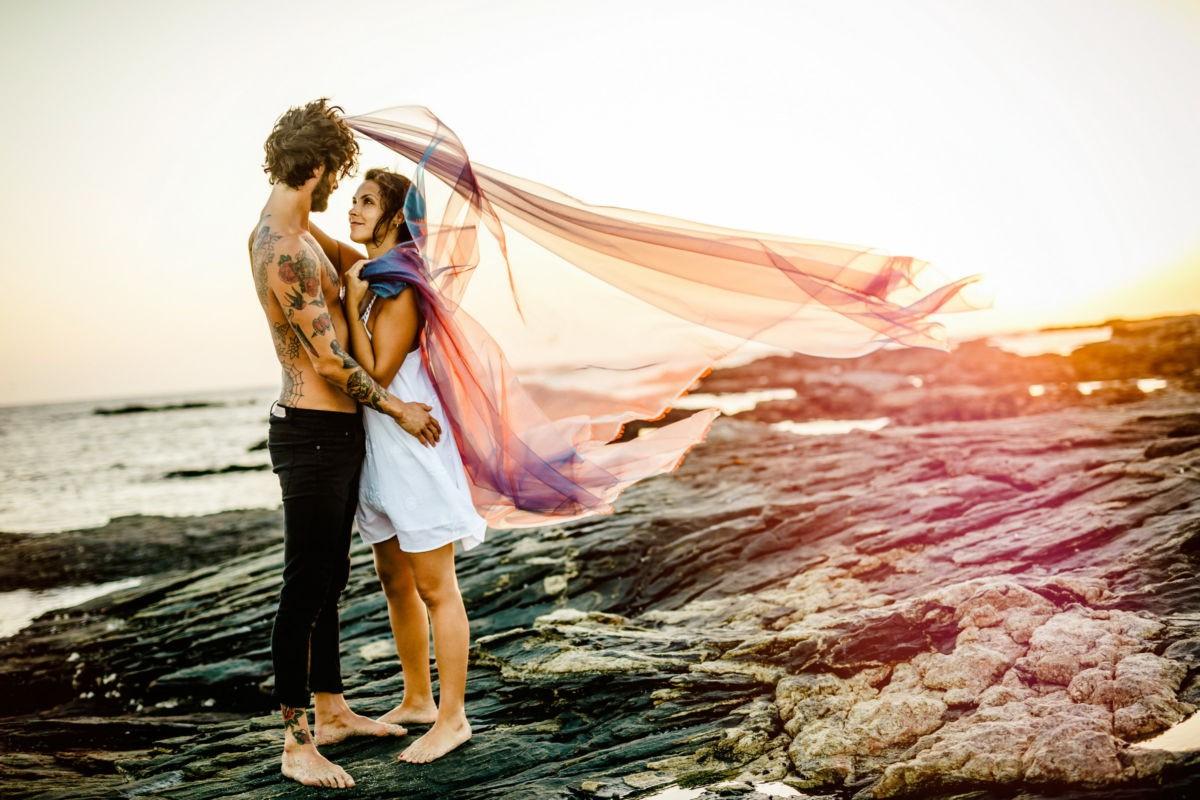 Ein Paar steht sich auf einem felsigen Strand gegenüber und sieht sich in dei Augen. Der Wind weht ein großes Tuch über ihnen zurück. Paar Fotos am Strand mit ROCKSTEIN fotografie