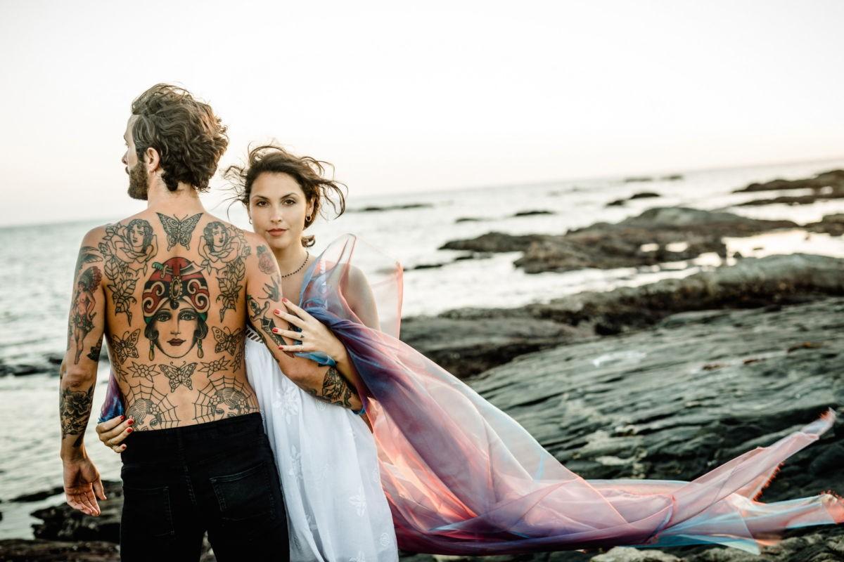 Ein Paar steht auf einem felsigen Strand. Der Mann ist von hinten zu sehen. Die Frau sieht in die Kamera. Wind zerzaust ihr Haar. Engagement Shooting.