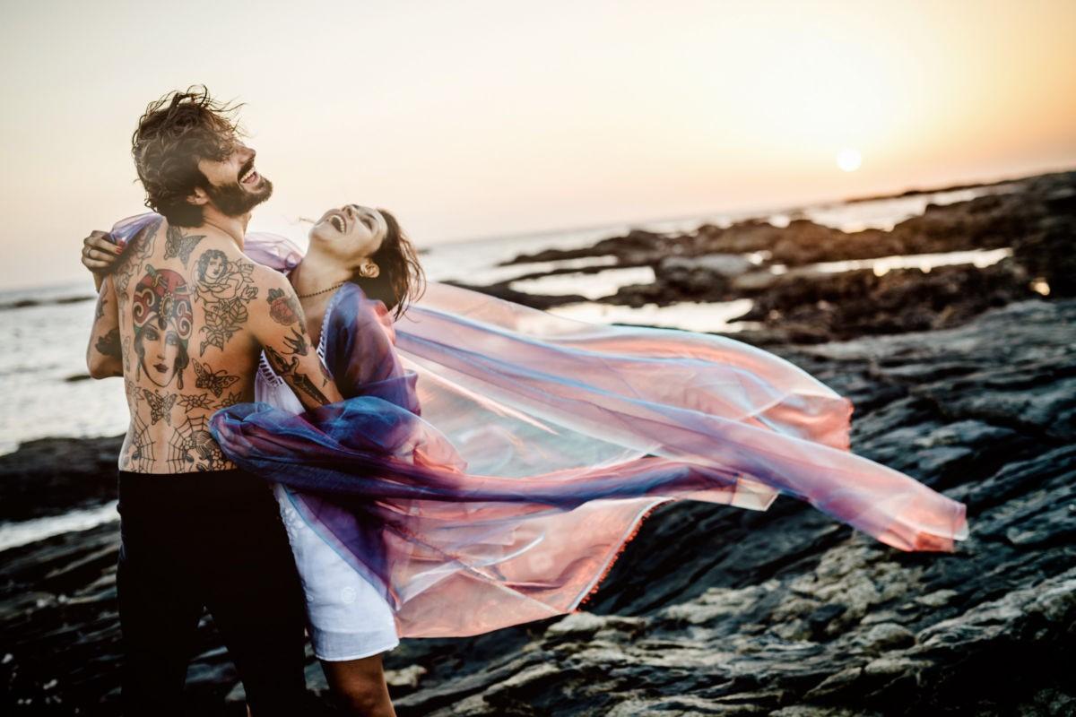 Ein Paar liegt sich am Strand in den Armen und lacht herzhaft. Paarshooting.