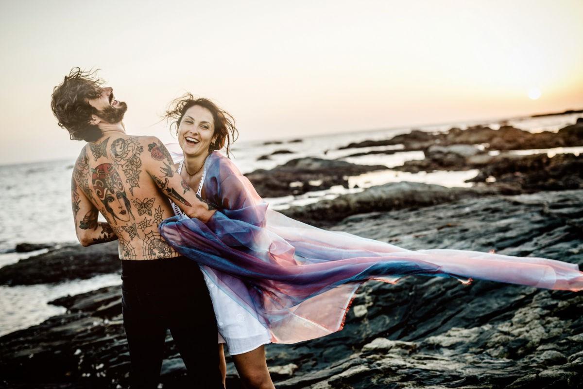 Ein Paar liegt sich am Strand in den Armen udn lacht. Paarshooting am Strand.