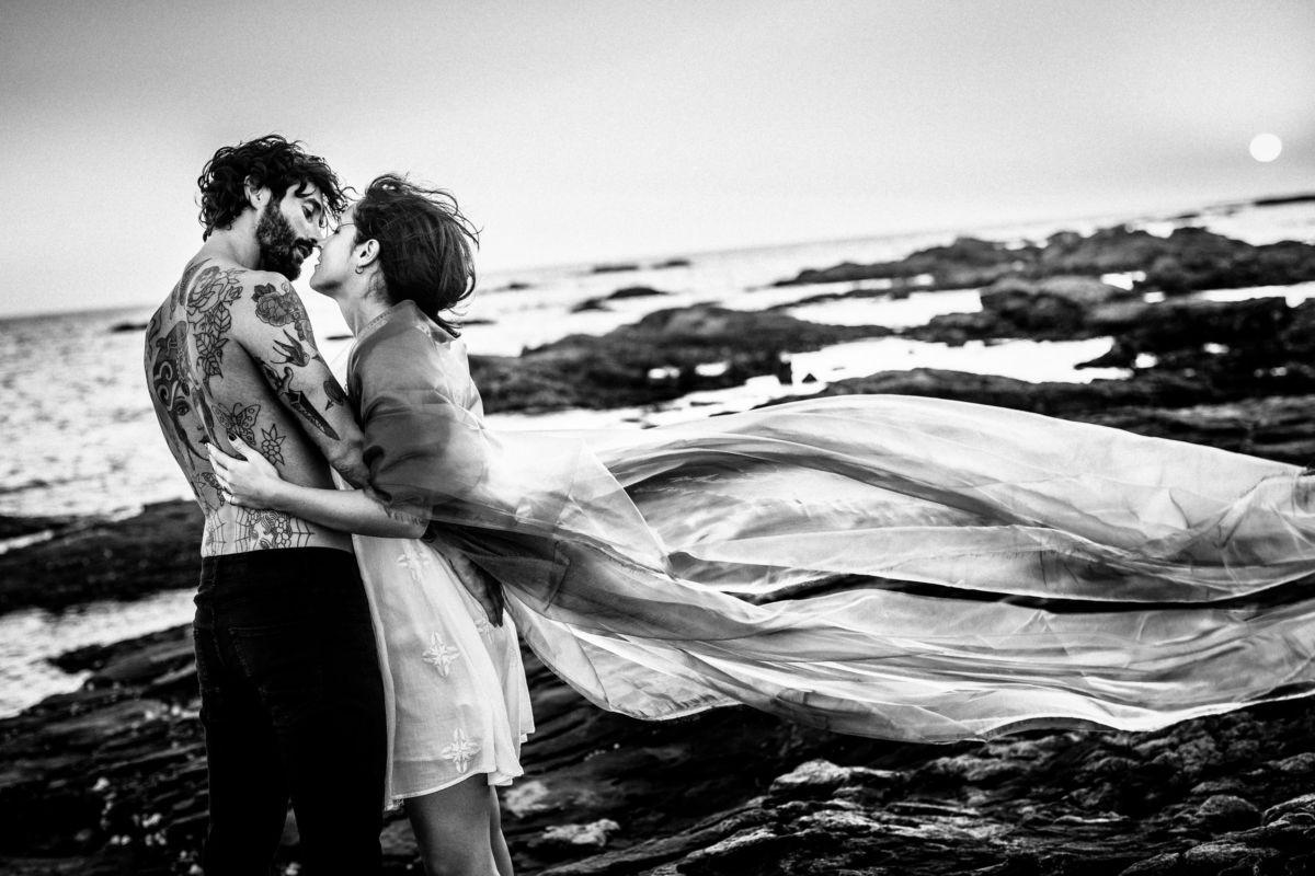 Ein Paar steht auf einem felsigen Strand und küsst sich. Der Wind weht ein Tuch hinter ihnen. Das Bild ist schwarz weiß. Paar Shooting.