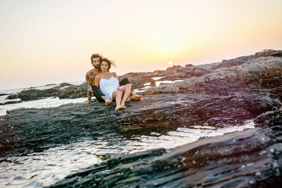 Ein Paar sitzt auf einem felsigen Strand im Sonnenuntergang.