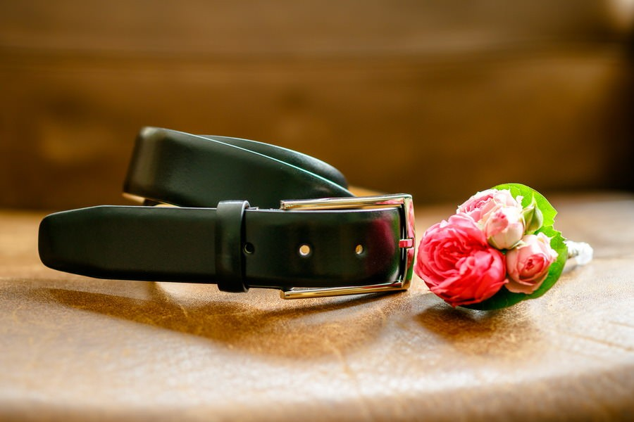 Gürtel und ansteckblume liegen auf einem Ledersessel und werden vom Hochzeitsfotografen Moers festgehalten
