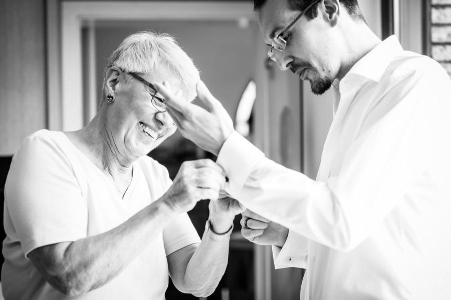 Die Mutter hilft dem Bräutigam beim Ankleiden der Manschettenknöpfe