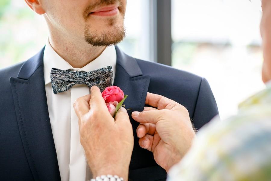 die Mutter hjlft dem Bräutigam die Ansteckblume anzuziehen