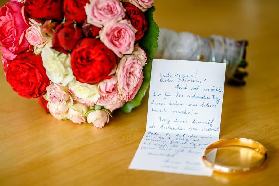 ein Brautstrauß liegt mit einem goldenen Armreif und einem Brief an die Braut auf einem Tisch