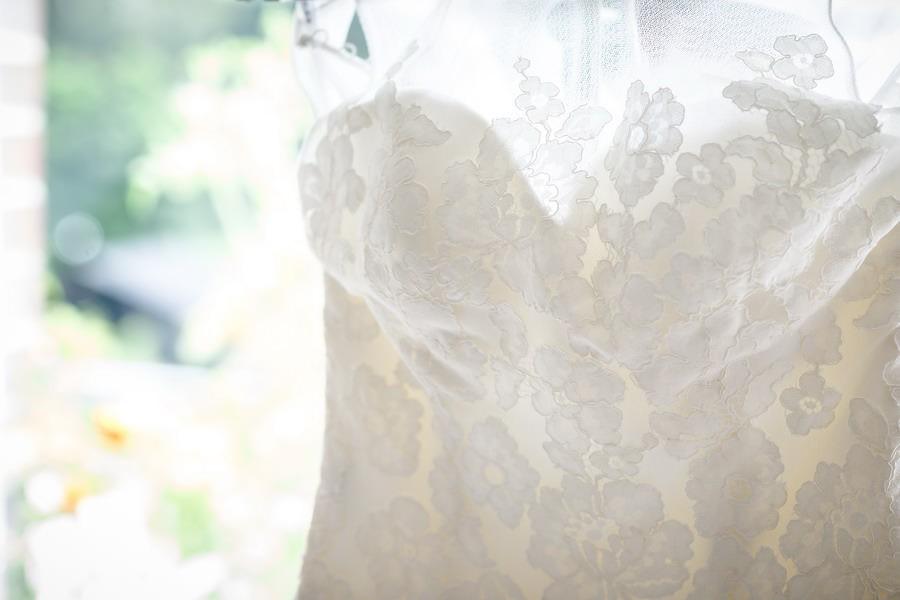 das Hochzeitskleid im Detail fotografiert vor einem Fenster