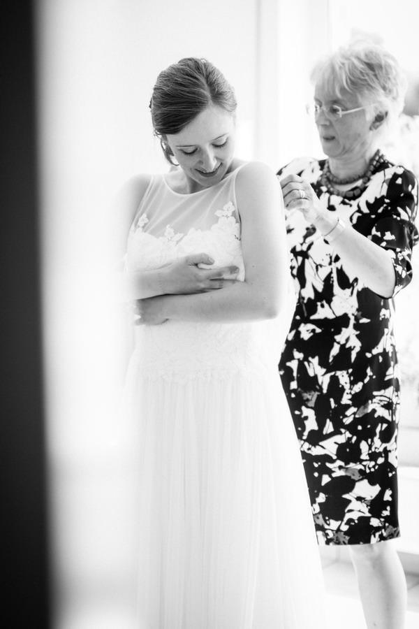die Brautmutter hilft der Braut beim Schließen des Brautkleides