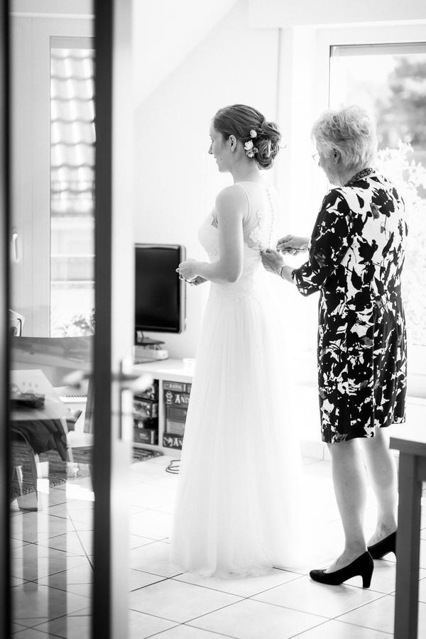 Die Brautmutter schließt das Brautkleid der Braut