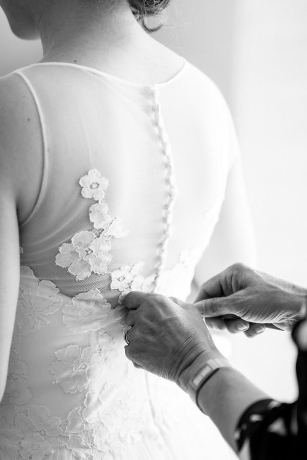 Mit einer Häkelnadel werden die Knöpfe des Brautkleids geschlossen