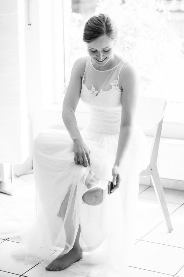 Die Braut sitzt in ihrem Brautkleid auf einem Stuhl und zieht sich ihre Brautschuhe an