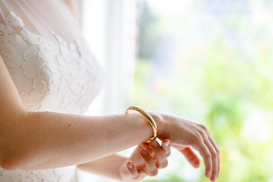 Ein goldener Armreif ziert den Arm einer Braut im Brautkleid