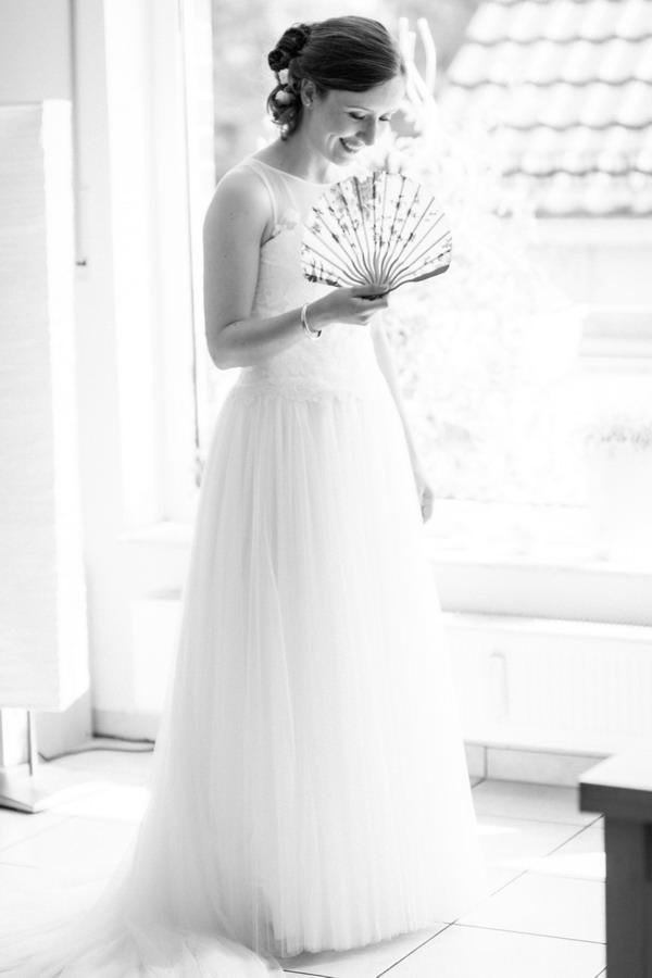 eine Braut steht in ihrem Brautkleid mit einem Fächer vor einem großen Fenster und lächelt