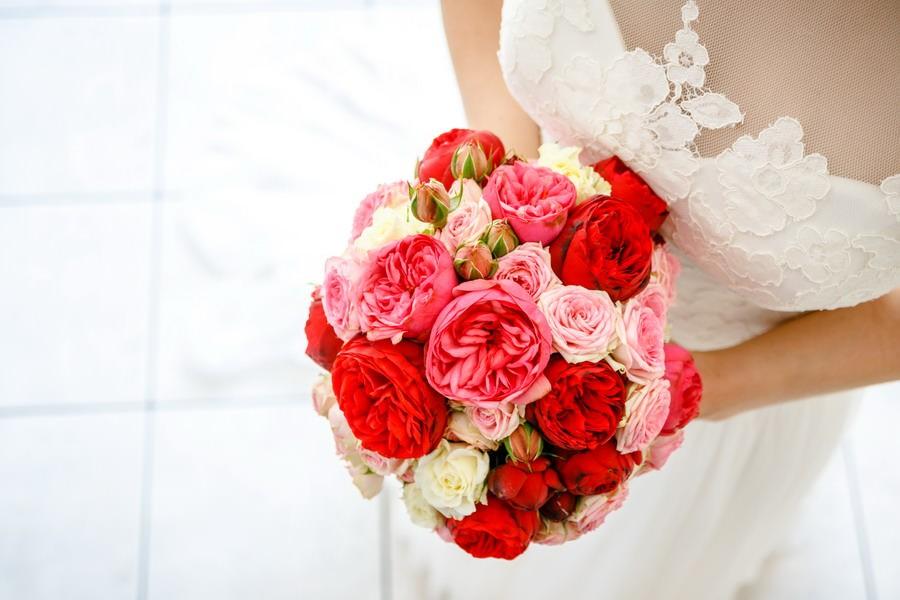 der Brautstrauß mit roten und pinken Pfingsrosen in den Händen der Braut im Brautkleid von oben fotografiert