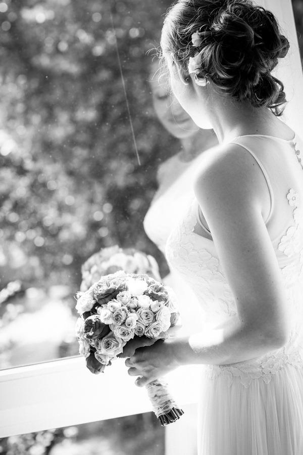 eine Braut steht vor einem Fenster und spiegelt sich in der Scheibe
