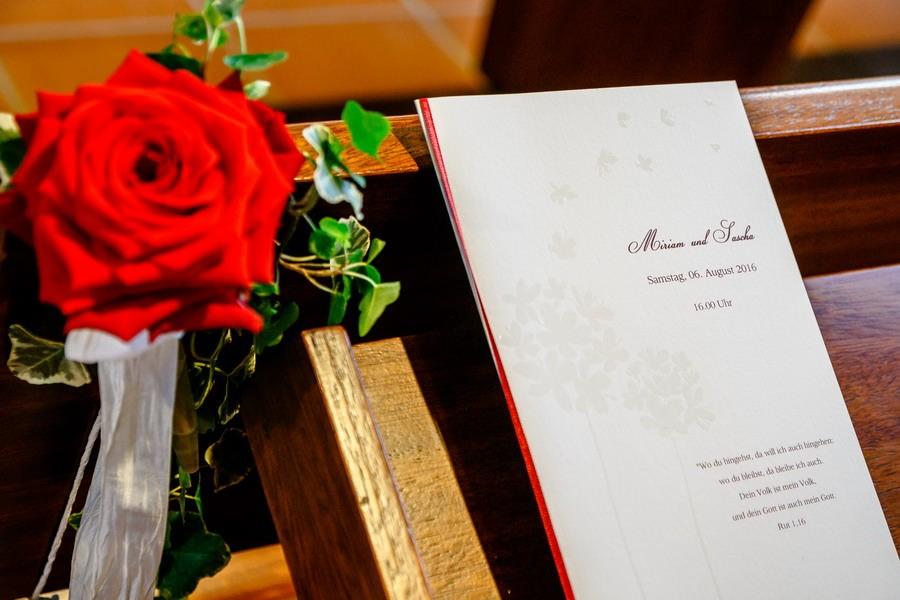 auf der Kirchenbank aus Holz liegt neben einer roten Rose ein Kirchenheft zur Hochzeit