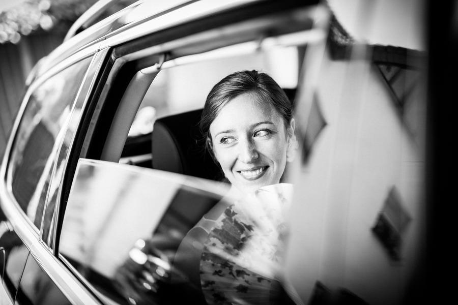 Die Braut sitzt im Auto und lächelt aus dem halb geöffnetem Fenster