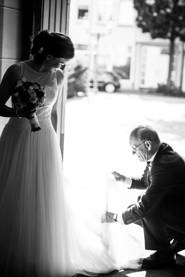 im Kircheneingang steht die Braut während ihr Vater das Kleid zurecht legt
