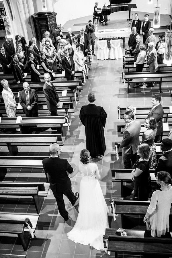 die Braut geht am Arm ihres Vaters den Kirchengang hinter dem Pfarrer her.