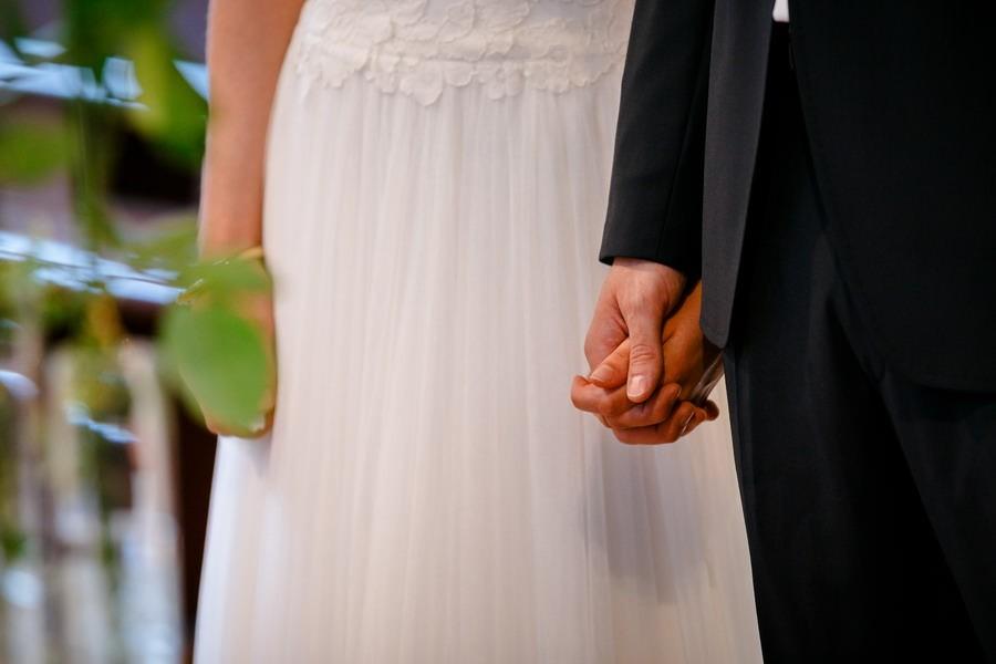 die verschlungenen Hände von Braut und Bräutigam sind in Nahaufnahme zu sehen