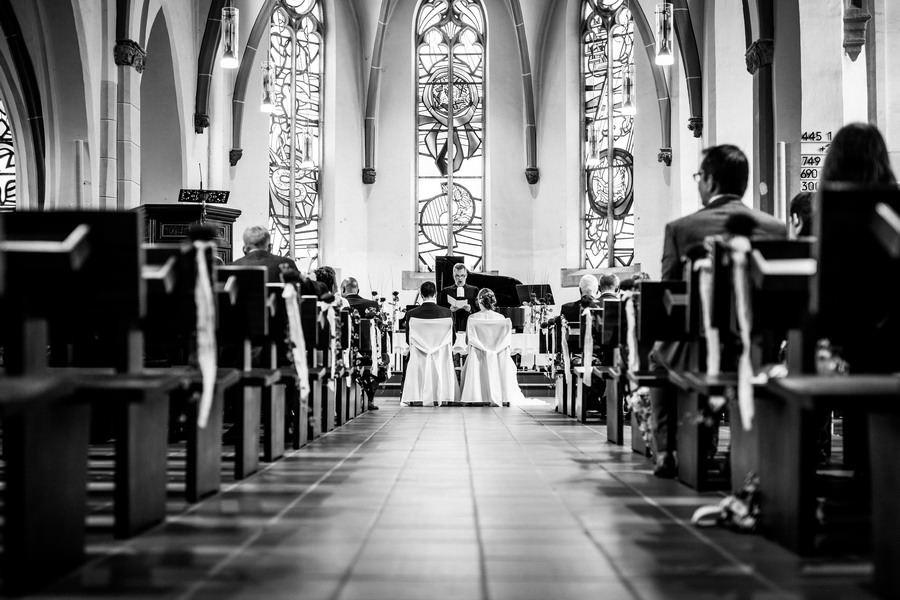 aus der Froschperspektive sieht man von hinten Braut und Bräutigam vor dem Altar sitzen