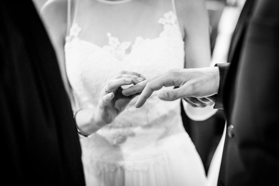 die Hände von Braut und Bräutigam in Nahaufnahe, während sie ihm den Ehering ansteckt